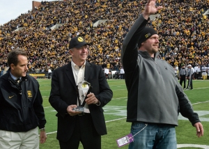 Jared DeVries waves to the crowd at Kinnick Stadium after joining the America Needs Farmers Wall of Honor.